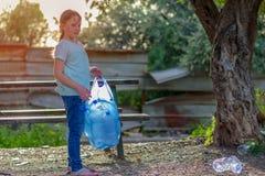 Limpieza del ni?o en parque Ni?o voluntario con un bolso de basura que limpia la litera, poniendo la botella pl?stica en el recic imagenes de archivo