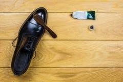 Limpieza del zapato fijada en fondo de madera Fotos de archivo