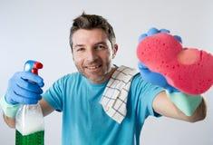 Limpieza feliz sonriente de la casa del marido que hace ocupado con la botella del espray y el vidrio que se lava de la esponja imagenes de archivo