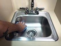 Limpieza que limpia un fregadero del cuarto de baño Imagen de archivo