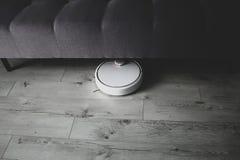 Limpieza robótica debajo del sofá, progreso tecnológico, efecto mate del aspirador fotografía de archivo