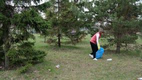 Limpieza voluntaria de la mujer para arriba la basura en el parque De la cosecha basura pl?stica para arriba al aire libre Concep almacen de video