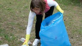 Limpieza voluntaria de la mujer para arriba la basura en el parque De la cosecha basura pl?stica para arriba al aire libre Concep metrajes
