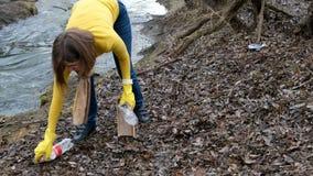 Limpieza voluntaria de la mujer para arriba la basura por el río De la cosecha basura para arriba al aire libre Concepto de la ec almacen de video