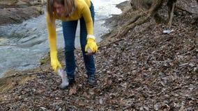 Limpieza voluntaria de la mujer para arriba la basura por el río De la cosecha basura para arriba al aire libre Concepto de la ec metrajes