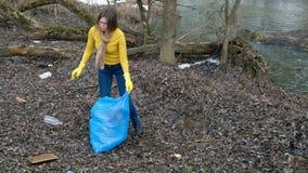 Limpieza voluntaria de la mujer para arriba la basura por el r?o De la cosecha basura para arriba al aire libre Concepto de la ec almacen de metraje de vídeo