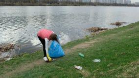 Limpieza voluntaria de la mujer para arriba la basura por el r?o De la cosecha basura para arriba al aire libre Concepto de la ec almacen de video