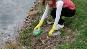Limpieza voluntaria de la mujer para arriba la basura por el r?o De la cosecha basura para arriba al aire libre almacen de video