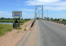Limpopo, Mozambique - December 11, 2008: Two unknown women stand. Near a street sign. The bridge and the road bridge over the river Limpopo Royalty Free Stock Photos