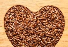 Lin oléagineux cru de graines de lin en forme de coeur Photo libre de droits