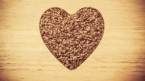 Lin oléagineux cru de graines de lin en forme de coeur Photos stock