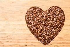 Lin oléagineux cru de graines de lin en forme de coeur Photo stock