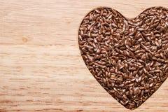 Lin oléagineux cru de graines de lin en forme de coeur Images stock