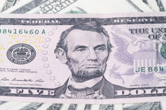 Lincoln on five dollar over heap of dollars United States as a background Stock Images