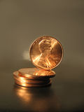Lincoln Makes Cents. A penny balancing on a stack of other pennies Stock Images