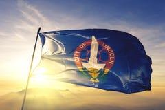 Lincoln-Stadthauptstadt von Nebraska des Flaggentextilstoffgewebes Vereinigter Staaten, das auf den Spitzensonnenaufgangnebelnebe stockfotos
