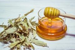 Lind och honung på den vita trätabellen Arkivfoto