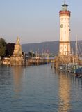 Lindau Lighthouse Afternoon. Port entrance to Lindau with lighthouse, Germany. Hills in the distance belong to Austria Stock Images