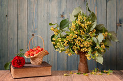 Linden flowers in a ceramic vase and cherries Royalty Free Stock Photography