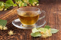 Linden herbal tea. Linden herbal tea with lime tree twigs with blossoms on wooden table royalty free stock photo
