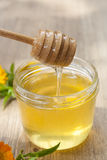 Linden honey in jar and calendula blossoms on wooden table Stock Photo