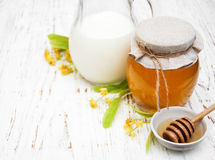 Linden honey and milk. On a old wooden background Royalty Free Stock Photos