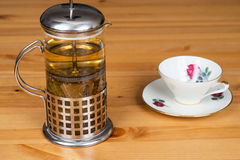 Linden tea in a french press with a mug. On a wooden surface Stock Image