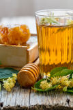 Linden tea in a glass and honey. Stock Photos