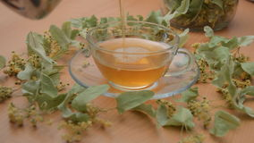 Linden Tea Poured into Transparent Cup. Footage of green tea being poured into a transparent cup surrounded by linden leaves. And a a jar with the leaves can stock footage