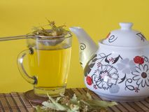 Linden tea and teapot with yellow background Royalty Free Stock Photo