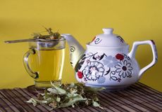 Linden tea and teapot with yellow background Stock Images