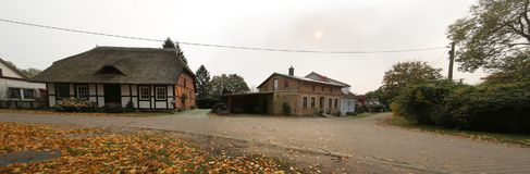 Lindenalle in Reinberg, Germany, with various historic buildings and faint sun creating a twilight mood stock photo