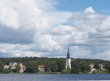 Lindesberg, a small town in Sweden. Water with a small town  and a white church with a blue sky and clouds Stock Photo