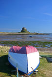 Lindisfarne. Castle with the harbour and a fishing boat  in the foreground Stock Photography