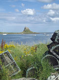 Lindisfarne Castle, Holy Island. Seen from the beach with its jumble of lobster pots Royalty Free Stock Image