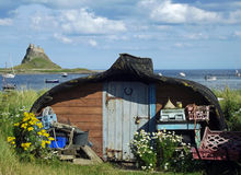 Lindisfarne Castle, Holy Island. Seen from the harbour, with an upturned Northumbrian coble, a traditional fishing boat, used now as a boat shed Royalty Free Stock Photo