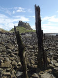 Lindisfarne Castle, Holy Island. Seen from the stony beach below, with the weathered remains of an old jetty Stock Photos