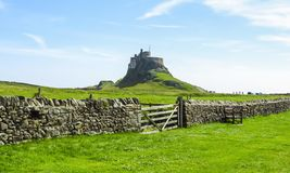 Lindisfarne Castle panoramic view, rock fence and wooden gate, Holy Island, Northumberland. UK royalty free stock photography