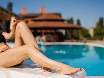 Lindo, bastante y piernas atractivas del ` s de la mujer joven en un fondo de la piscina fotos de archivo