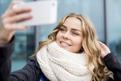 Lindo, chica joven que toma el selfie por el teléfono celular al aire libre en día del otoño Fotografía de archivo libre de regalías