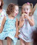 Lindo chlidren comiendo los buñuelos dulces Imagen de archivo