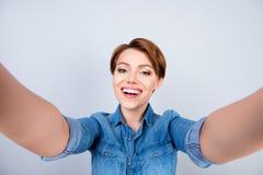 Lindo feliz con la mujer de la sonrisa de emisión en la camisa de los vaqueros que toma el selfie Fotos de archivo libres de regalías
