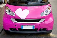 Lindo poco coche rosado con un corazón Foto de archivo
