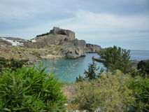 Lindos Acropolis, Rhodes, Greek Islands. View of Lindos with sea ocean bay in front. Turquoise seas and vegetation in the foreground Stock Images