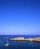 Lindos bay. Sailboat moored off the coast of the village of Lindos on the greek island of Rhodes royalty free stock images