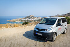 Rental Nissan Evalia is staying parked near Lindos town on Rhodes town, Greece. LINDOS, RHODES - AUGUST 2017: Rental Nissan Evalia is staying parked near Lindos Royalty Free Stock Images