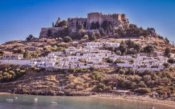 Lindos village and the endless Aegean sea photo taken from Kleovoulos Tomb hill. LINDOS,RHODES/GREECE OCTOBER 29 2018 : The Acropolis of Lindos and the village royalty free stock photos