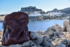 Backpack with the view of Lindos village and castle stock photo