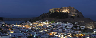 Lindos , Rhodes , Greece. Lindos ( Rhodes island , Greece ) with its white cube-shaped houses which combine Byzantine and Arabic styles and its acropolis sitting Stock Photos