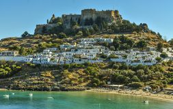 Lindos village and the endless Aegean sea photo taken from Kleovoulos Tomb hill. LINDOS,RHODES/GREECE OCTOBER 29 2018 : The Acropolis and the village of Lindos stock photography
